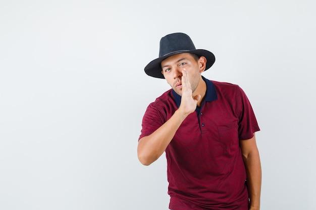 Junger mann erzählt geheimnis hinter der hand in t-shirt, hut und schaut neugierig, vorderansicht.