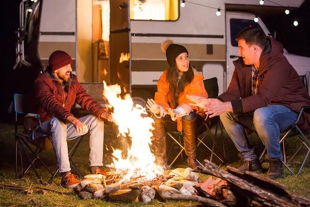 Junger mann erzählt seinen freunden am lagerfeuer in den bergen eine geschichte. retro wohnmobil im hintergrund mit glühbirnen.