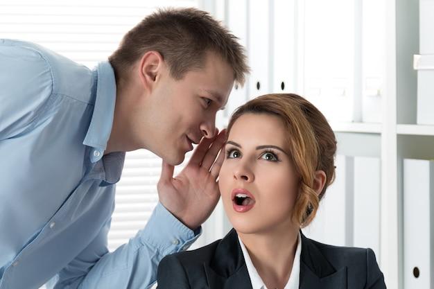 Junger mann erzählt seiner kollegin im büro klatsch und tratsch. intrigen und zeitverschwendung konzept