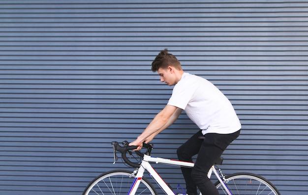 Junger mann fährt ein weißes straßenfahrrad gegen den hintergrund der wand
