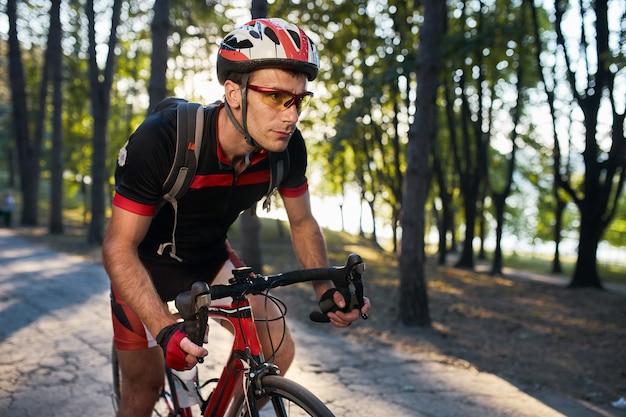 Junger mann fahren rennrad am abend rad