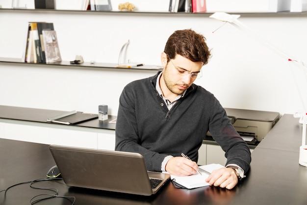 Junger mann fangen an, an schreibtisch zu arbeiten