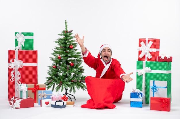 Junger mann feiern weihnachtsfeiertag, der im boden nahe geschenken und geschmücktem weihnachtsbaum sitzt
