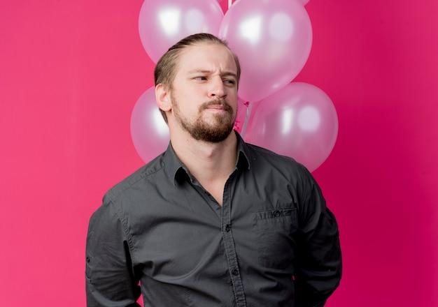 Junger mann feiert geburtstagsfeier, die bündel der luftballons hält, die beiseite stehen, verwirrt über rosa wand stehen