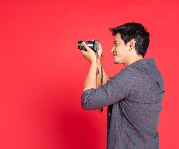 Junger mann findet etwas, um kamera zu schießen.