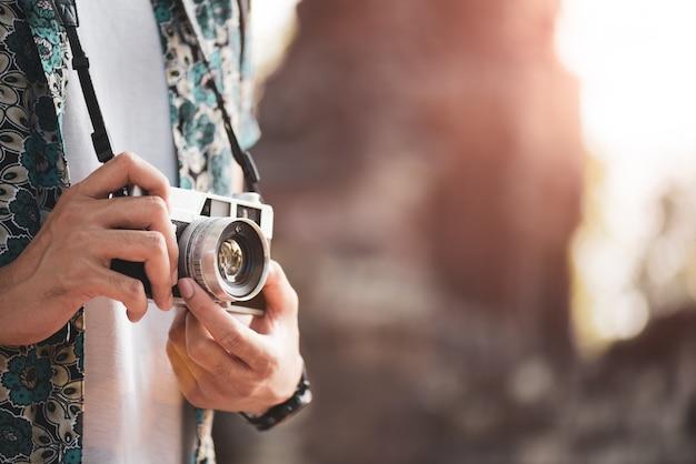 Junger mann-fotograf traveler mit dem rucksack, der foto macht