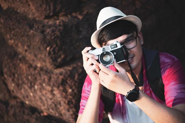 Junger mann-fotograf traveler mit dem rucksack, der foto mit seiner kamera macht