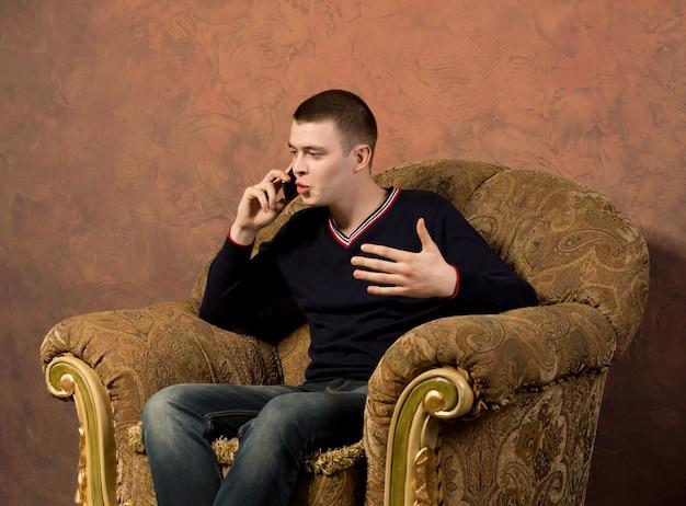 Junger mann führt ein animiertes gespräch auf seinem handy mobile