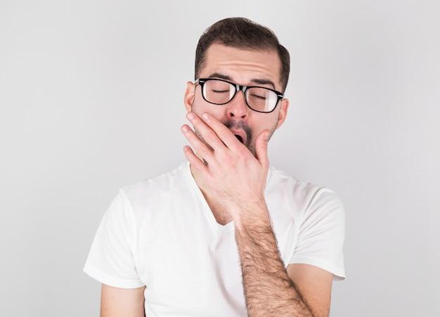 Junger mann gähnt vor müdigkeit gegen graue wand