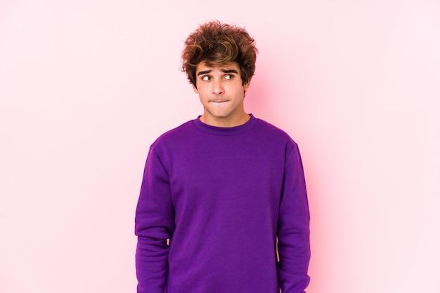 Junger mann gegen ein rosa verwirrt, fühlt sich zweifelhaft und unsicher.