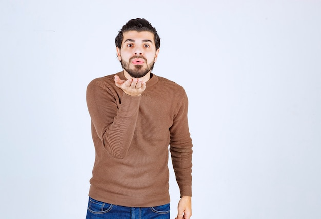 Junger mann gegen lippenfalten und handflächen, um luftkuss zu senden.
