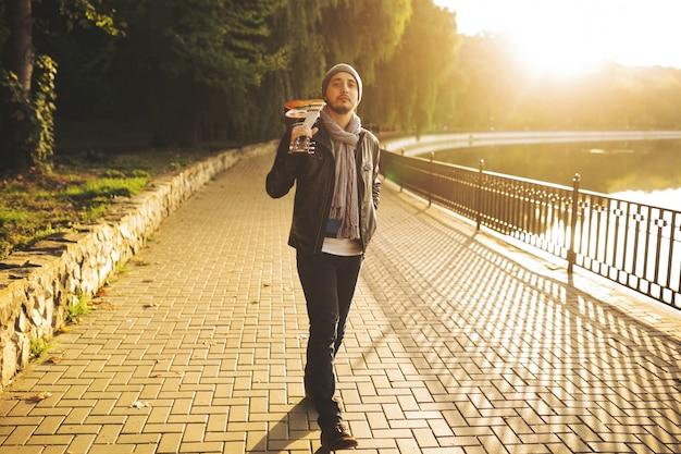 Junger mann geht am see entlang und hält gitarre