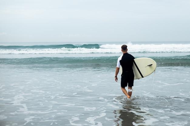 Junger mann geht surfen