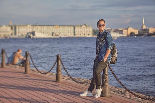 Junger mann geht über die uferpromenade des flusses newa mit rucksack in sankt petersburg, russland.