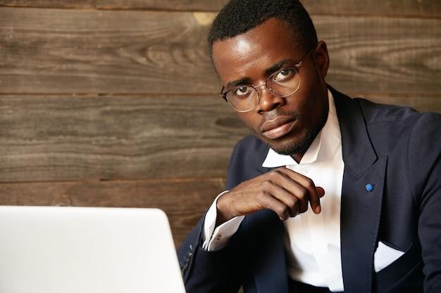 Junger mann gekleidet im formellen anzug unter verwendung des laptops