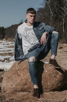 Junger mann gekleidet in lässigem jeans-outfit, das auf einem stein am kalten seeufer aufwirft.