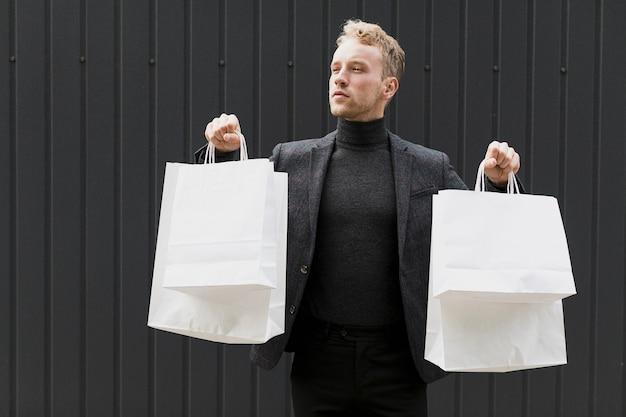 Junger mann, gekleidet in schwarz mit einkaufstüten