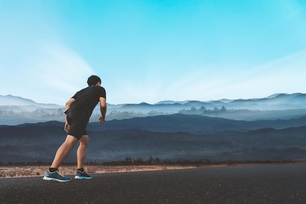 Junger mann genießen, draußen mit schönem sommerabend in der landschaft zu laufen.