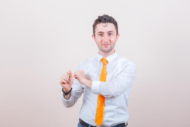 Junger mann gestikuliert, als ob er sich darauf vorbereitet, den pfeil in weißem hemd, jeans freizugeben