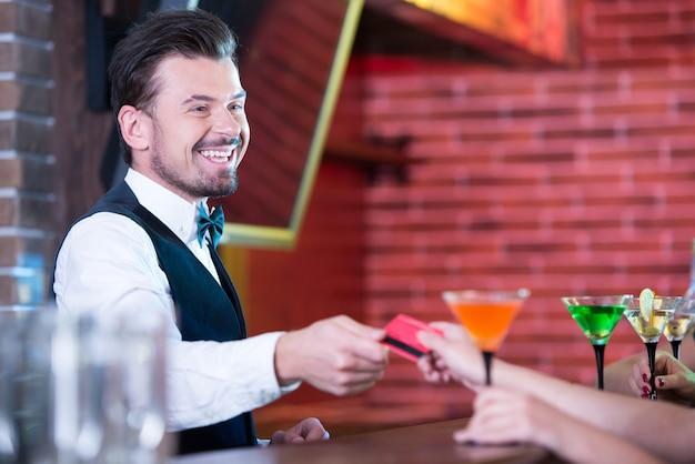 Junger mann gibt allen mädchen einen cocktail.