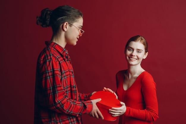 Junger mann gibt seiner freundin eine herzförmige schachtel am valentinstag auf rotem hintergrundstudio