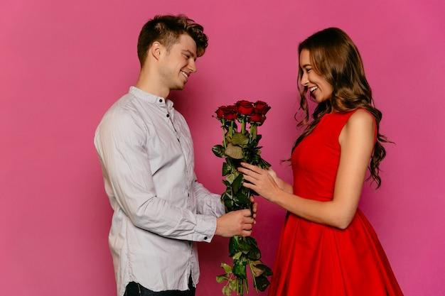 Junger mann gibt seiner herrlichen freundin rote rosen, gekleidet im roten kleid.
