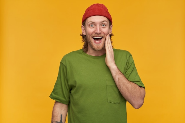 Junger mann, glücklicher kerl mit blonden haaren, bart und schnurrbart. trägt grünes t-shirt und rote mütze. hat tätowierung. er berührte seine wange. isoliert über gelbe wand