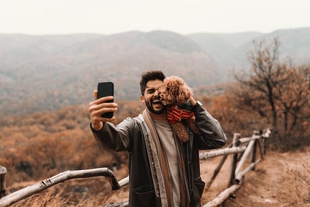 Junger mann hält auf schulter seinen aprikosenpudel und versucht, selbstporträt zu machen, während pudel sein gesicht leckt