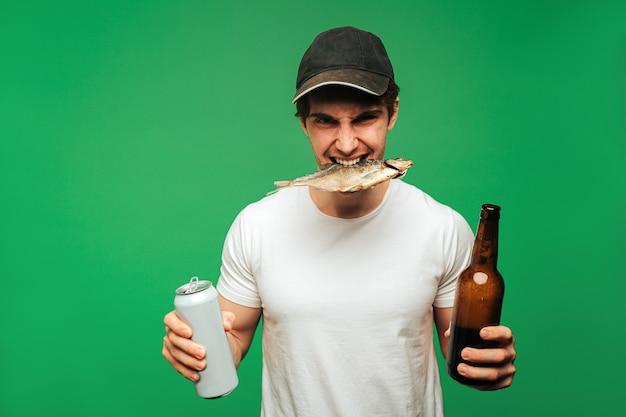 Junger mann hält bier und getrockneten fisch im mund