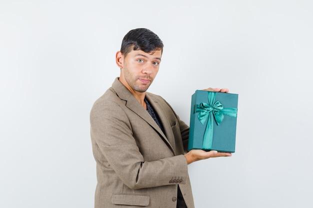 Junger mann hält blaue geschenkbox in graubrauner jacke und schaut selbstbewusst, vorderansicht.