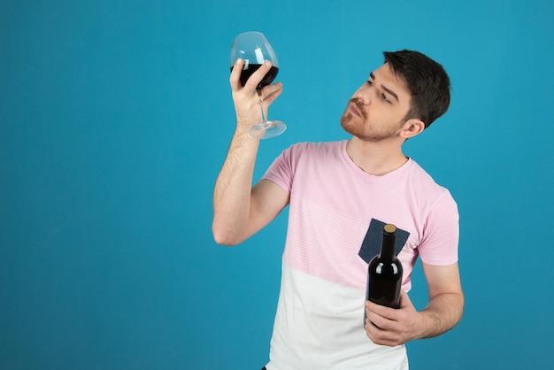 Junger mann hält ein glas wein hoch und betrachtet es.