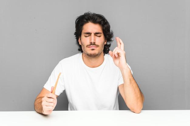 Junger mann hält eine zahnbürste, die finger kreuzt, um glück zu haben