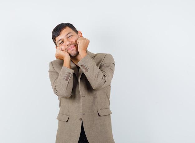Junger mann hält fäuste auf seinen wangen in graubrauner jacke und sieht liebenswert aus. vorderansicht.
