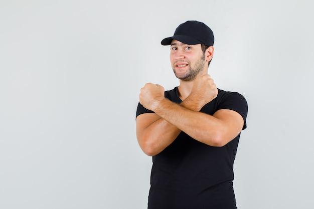 Junger mann hält fäuste gekreuzt in schwarzem t-shirt, mütze und sieht fröhlich aus