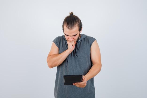 Junger mann hält faust auf mund im kapuzenpulli und schaut verwirrt, vorderansicht.