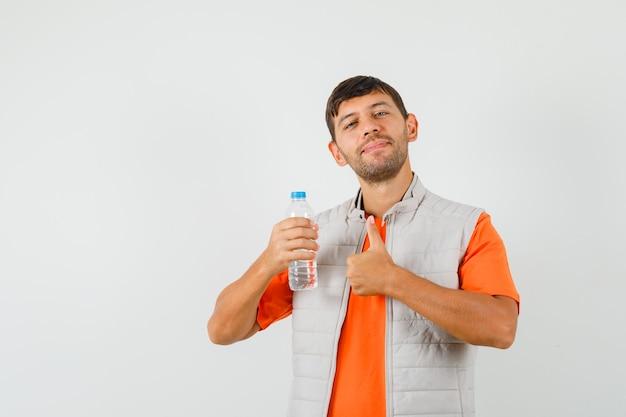 Junger mann hält flasche wasser, zeigt daumen oben in t-shirt, jacke und sieht erfreut aus. vorderansicht.