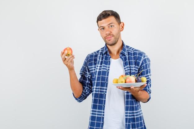 Junger mann hält frische früchte und lächelt in der vorderansicht des hemdes.