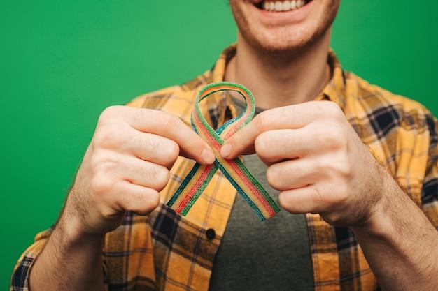 Junger mann hält geleebonbons wie rotes band