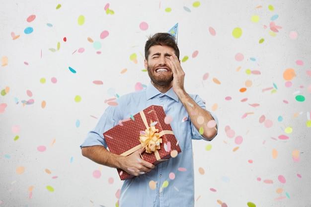 Junger mann hält geschenk umgeben von konfetti