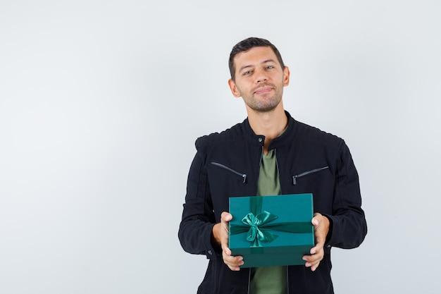 Junger mann hält geschenkbox in t-shirt, jacke und schaut froh, vorderansicht.