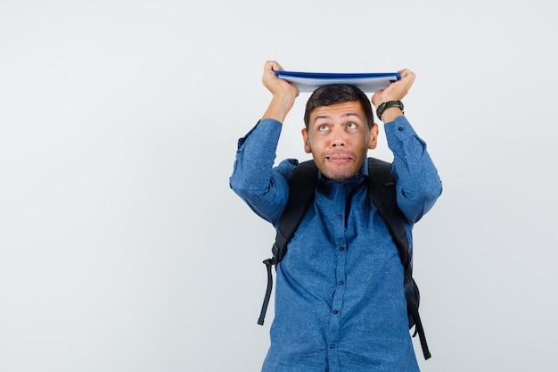 Junger mann hält klemmbrett auf dem kopf im blauen hemd und sieht lustig aus, vorderansicht.