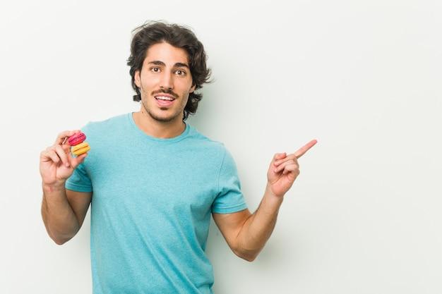 Junger mann hält makronen lächelnd und zeigt fröhlich mit dem zeigefinger weg.