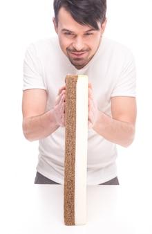 Junger mann hält matratze aus kokosfaser.