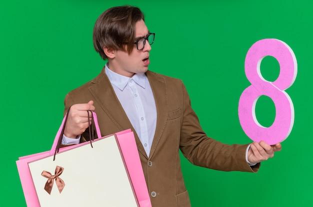 Junger mann hält papiertüten mit geschenken und nummer acht aus pappe, die es betrachten, verwirrte internationalen frauentag, der über grüner wand steht