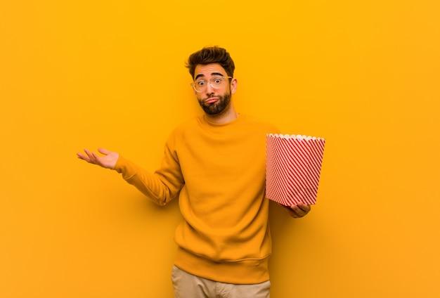 Junger mann hält popcorns zweifelnd und zuckt mit den schultern