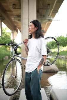 Junger mann hält sein fahrrad