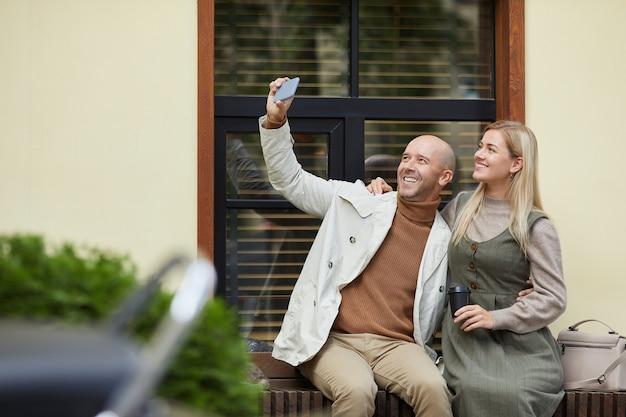 Junger mann hält sein handy und macht selfie-porträt mit seiner frau, während sie auf der straße sitzen