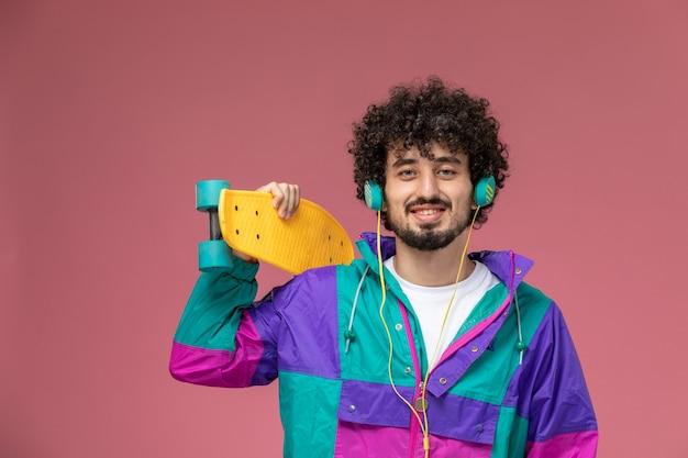 Junger mann hält sein neues gelbes scate board