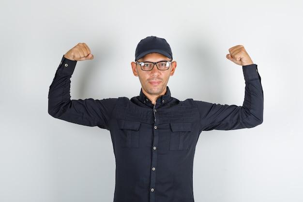 Junger mann hält seine arme in schwarzem hemd und mütze, brille und stark aussehend.