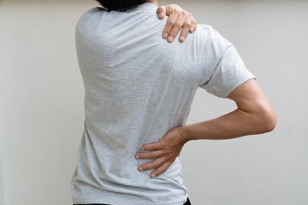 Junger mann hält seinen rücken vor schmerzen. medizinisches konzept